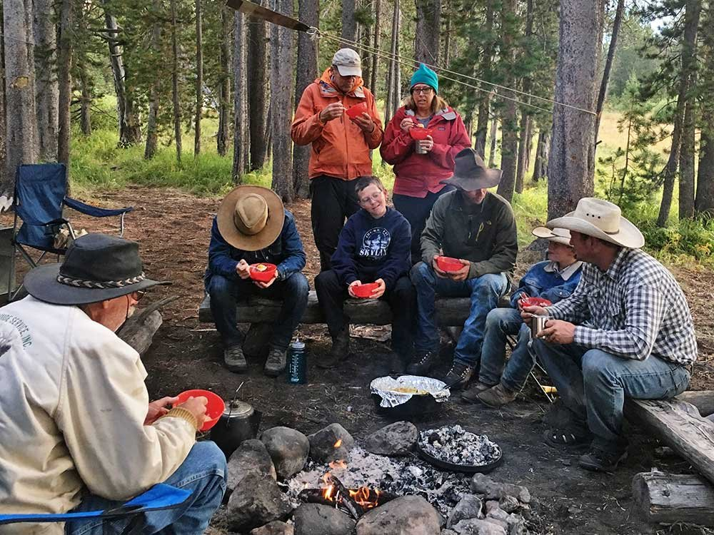 group gathered around campfire