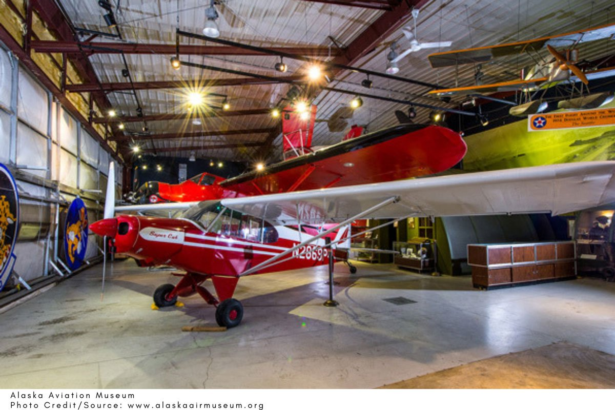 red prop plane on display in a hangar