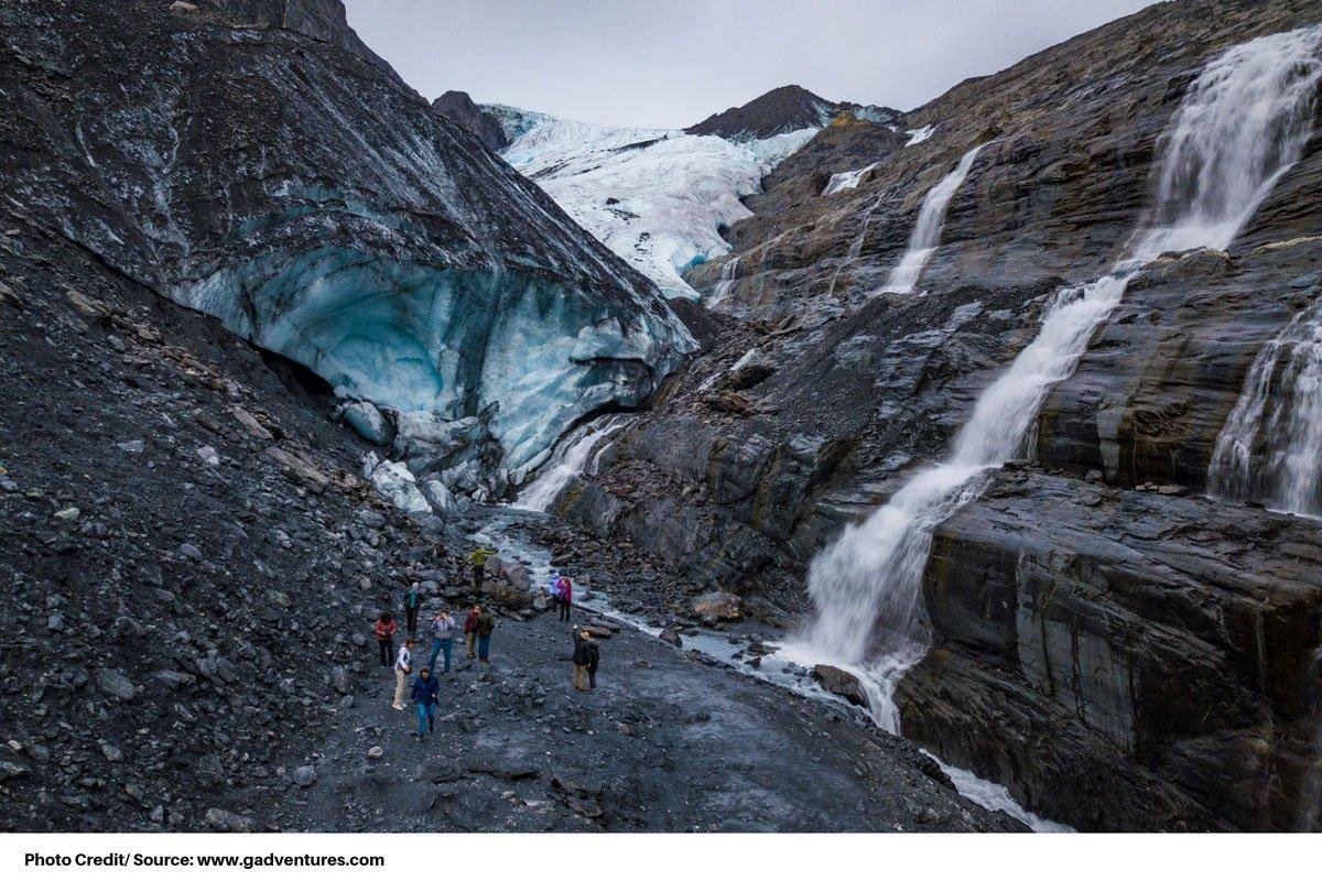 visitors hiking near glacier and waterfalls