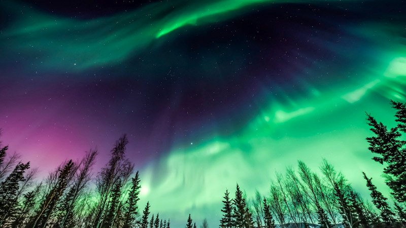 the Northern Lights shimmering in green and purple