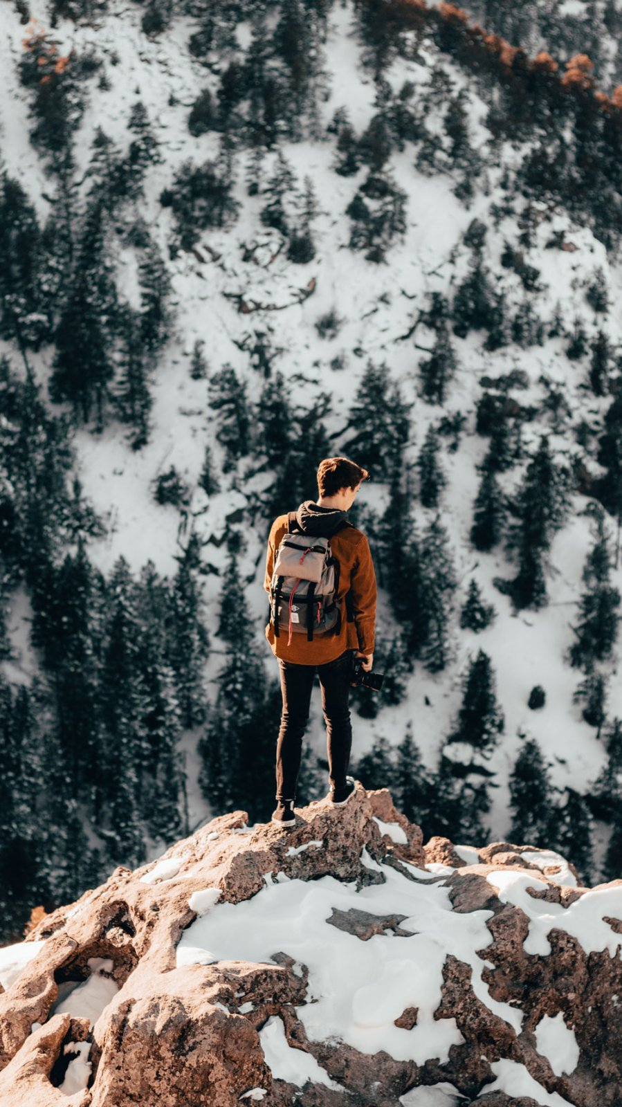 young photographer standing on a snowy peak