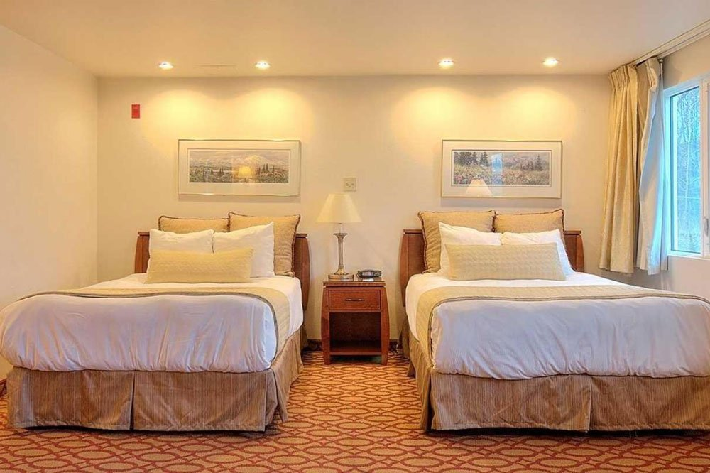 two double beds with white bedspreads