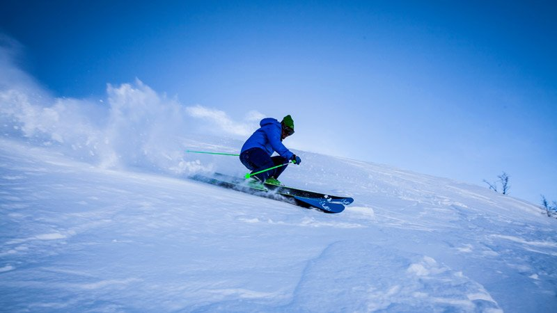 a skiier in blue gear going quickly down the mountain