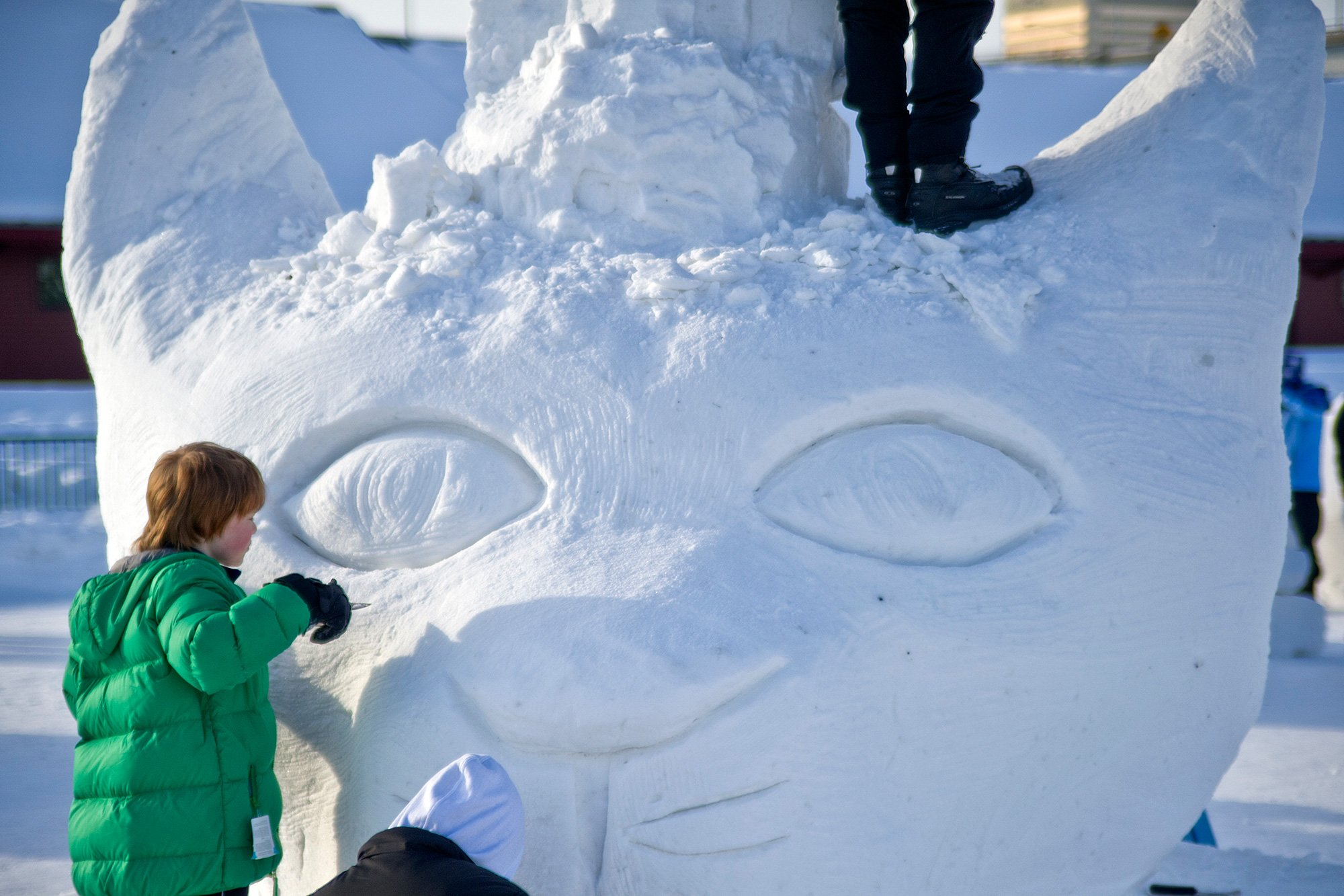 child carving snow sculpture