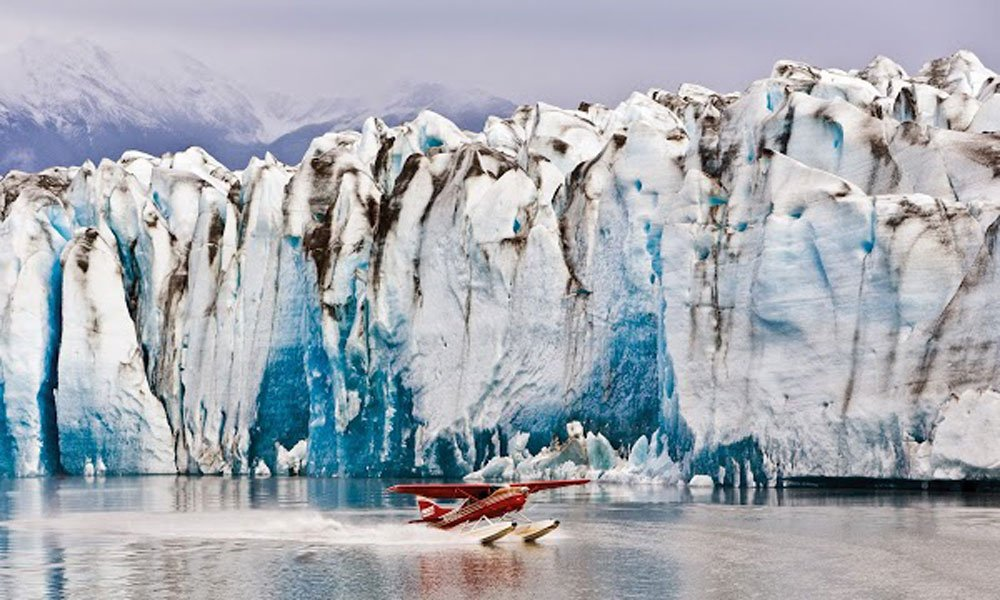 plane landing on water in front of glacier
