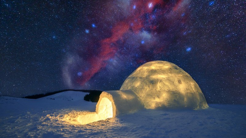 an igloo glowing from within, below the Northern Lights
