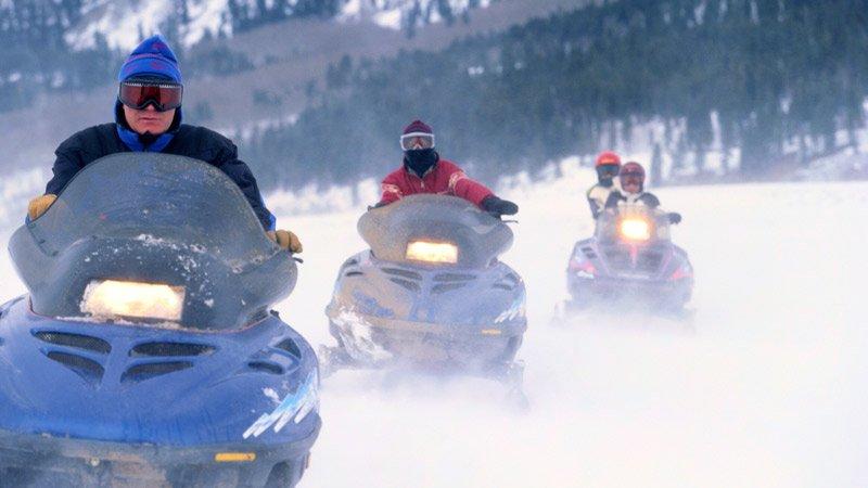 three snowmobile riders going single-file down a trail
