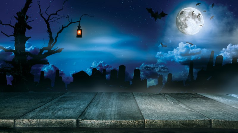 shadowy headstones and bats under the full moon