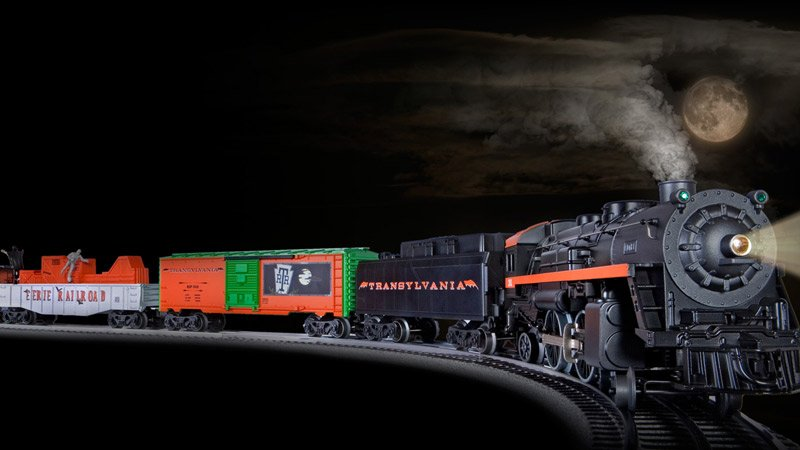 the full moon lights a spooky black and orange train