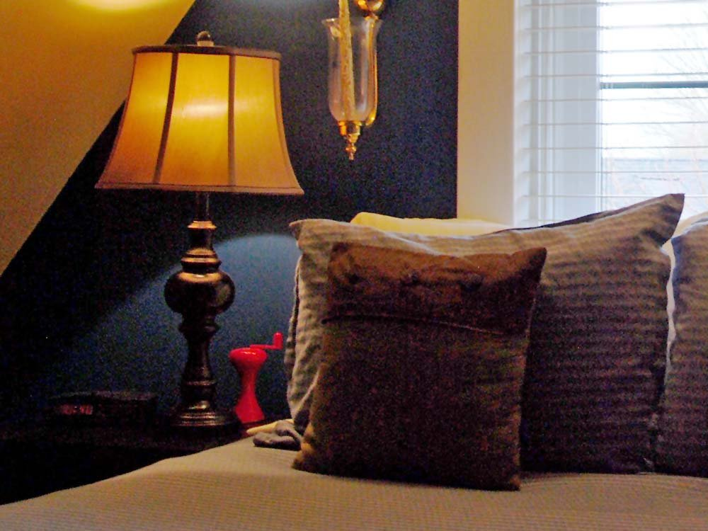brown pillow on bed near lamp
