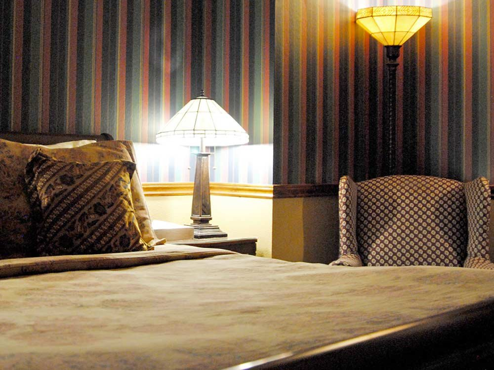 chair and lamp near bed with decorative pillow