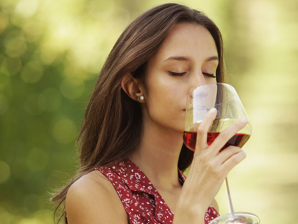 woman smelling glass of red wine