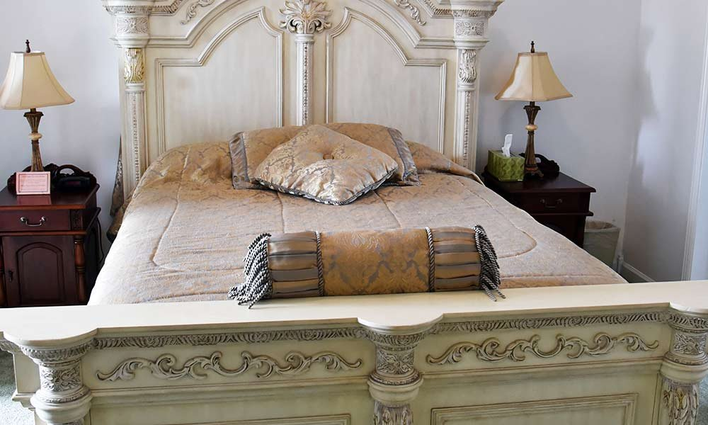 finely carved bed frame and pillows on the bed