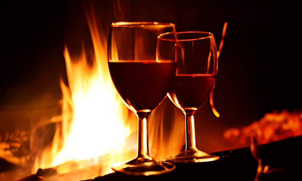 two glasses of red wine in front of fire
