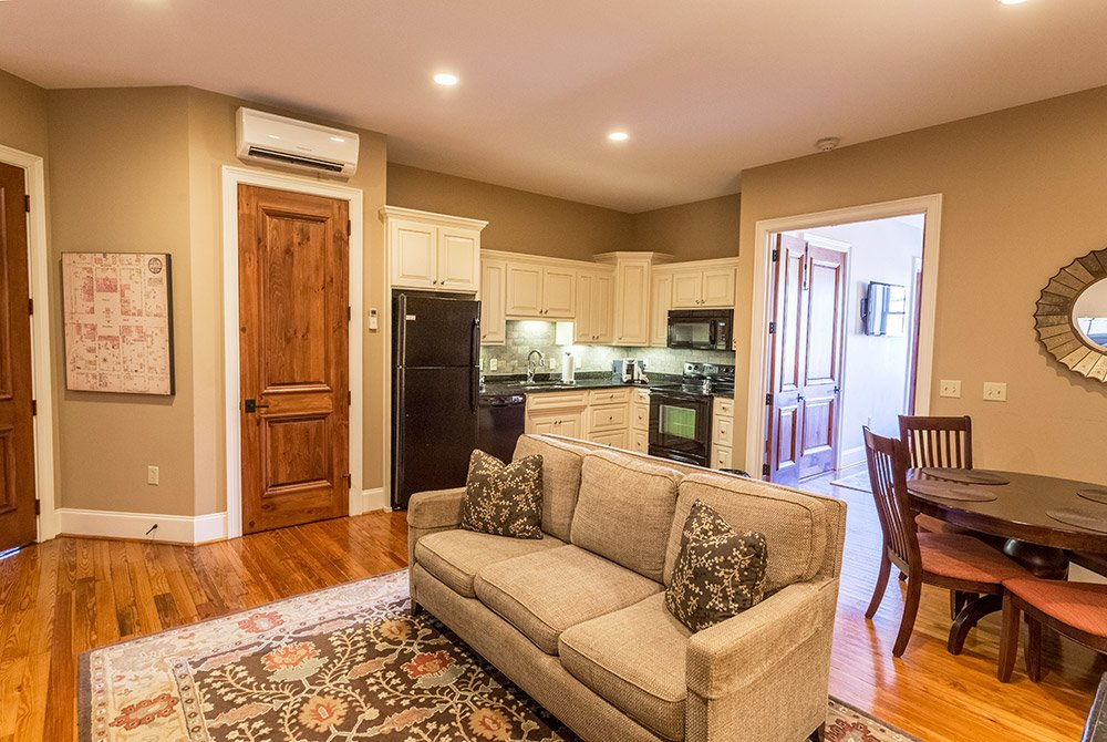 Couch next to coat closet, kitchen, and dining table