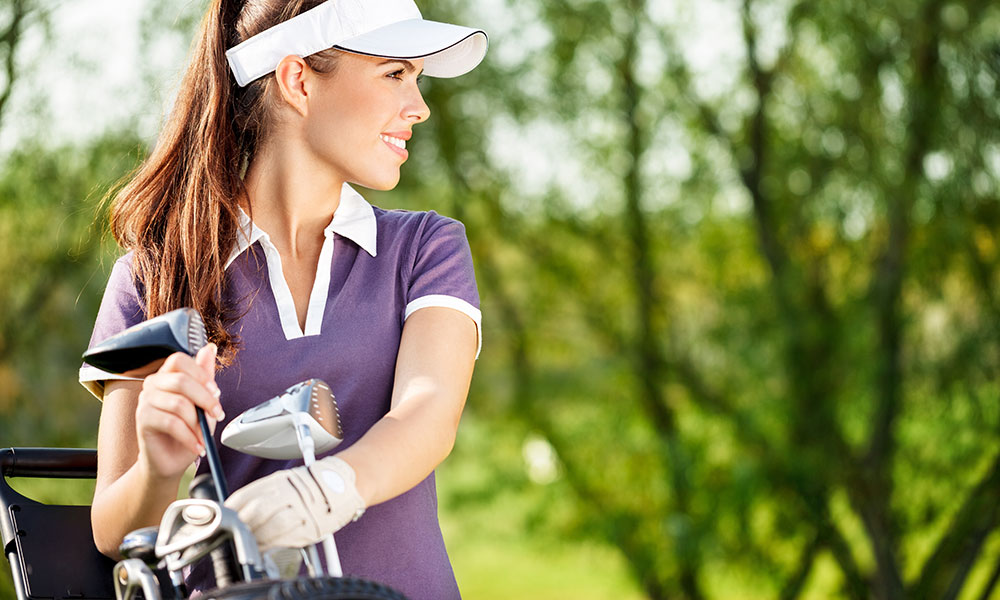 Woman pulling golf club out of bag