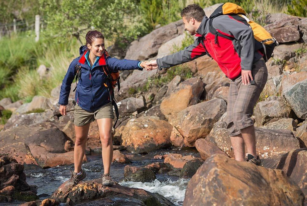two people hiking near rocks