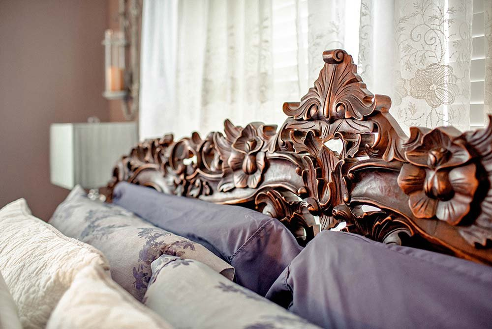 Pillows against garnished wood headboard