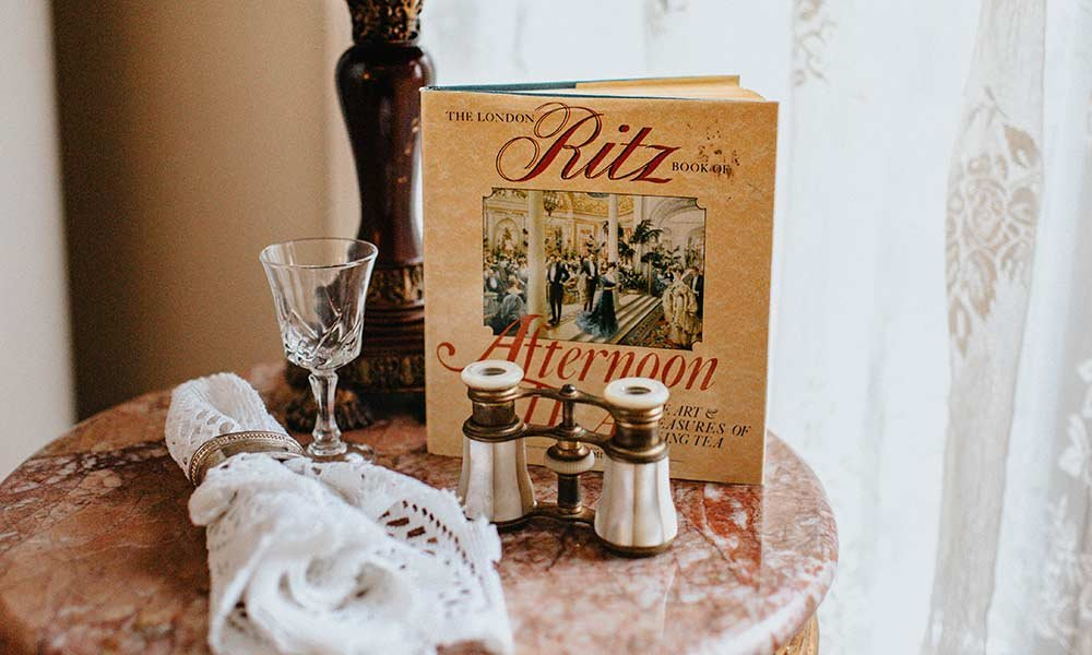 Book on table by candle holders and goblet