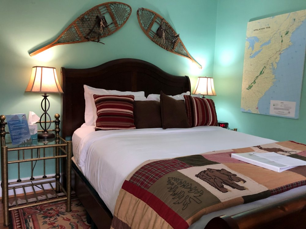 bed with lamps to either side, old snowshoes above bed, map to one side