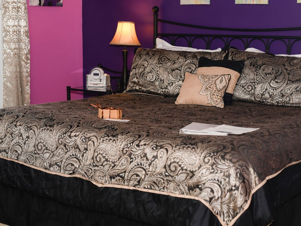 Decorative pillows and box of chocolates on king-sized bed