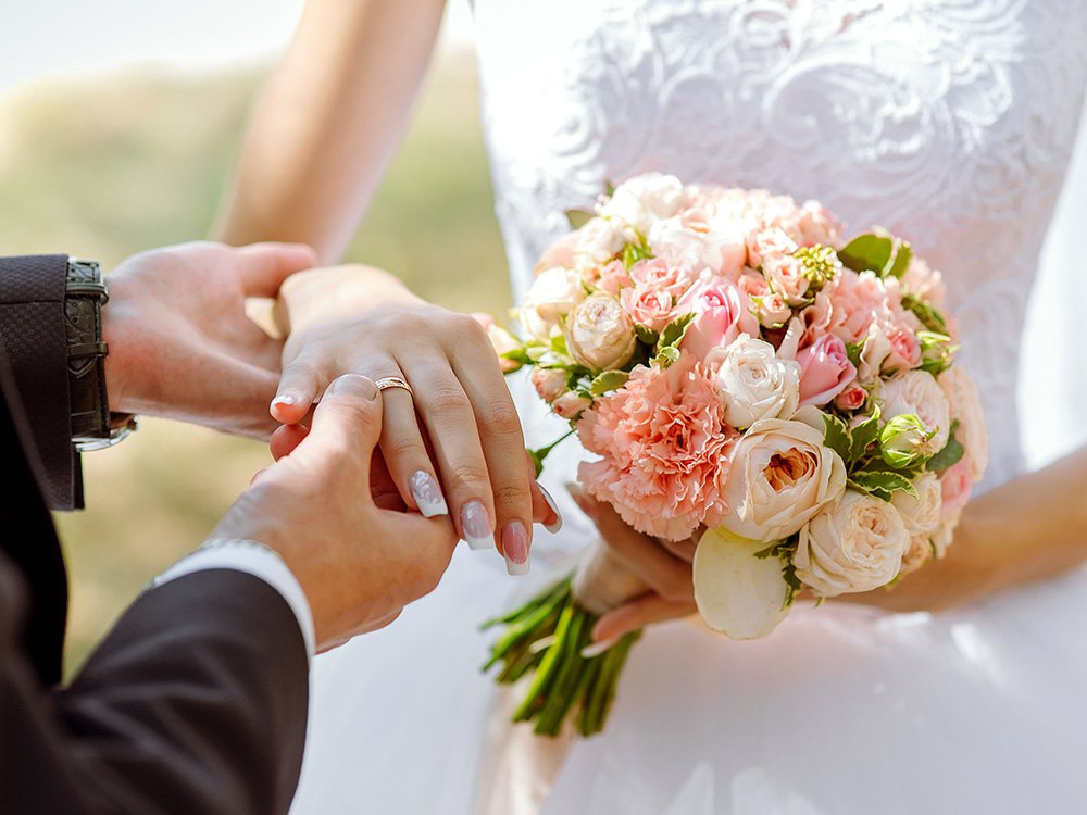 Groom holding brides' hand and boquet of flowers