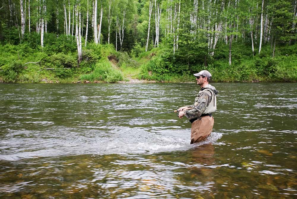 man fly fishin in river