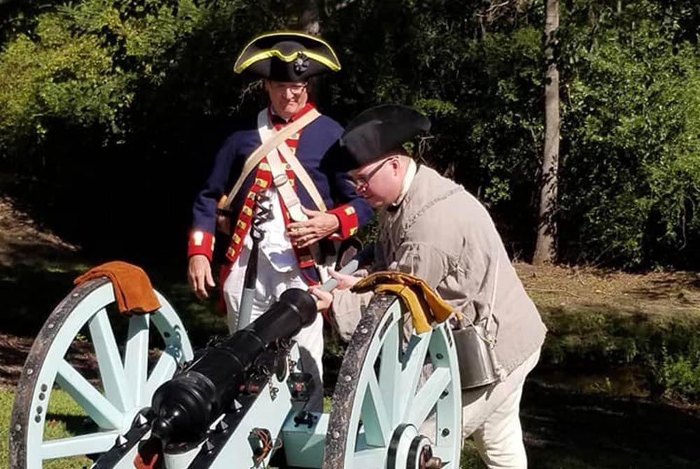 men loading a civil war cannon
